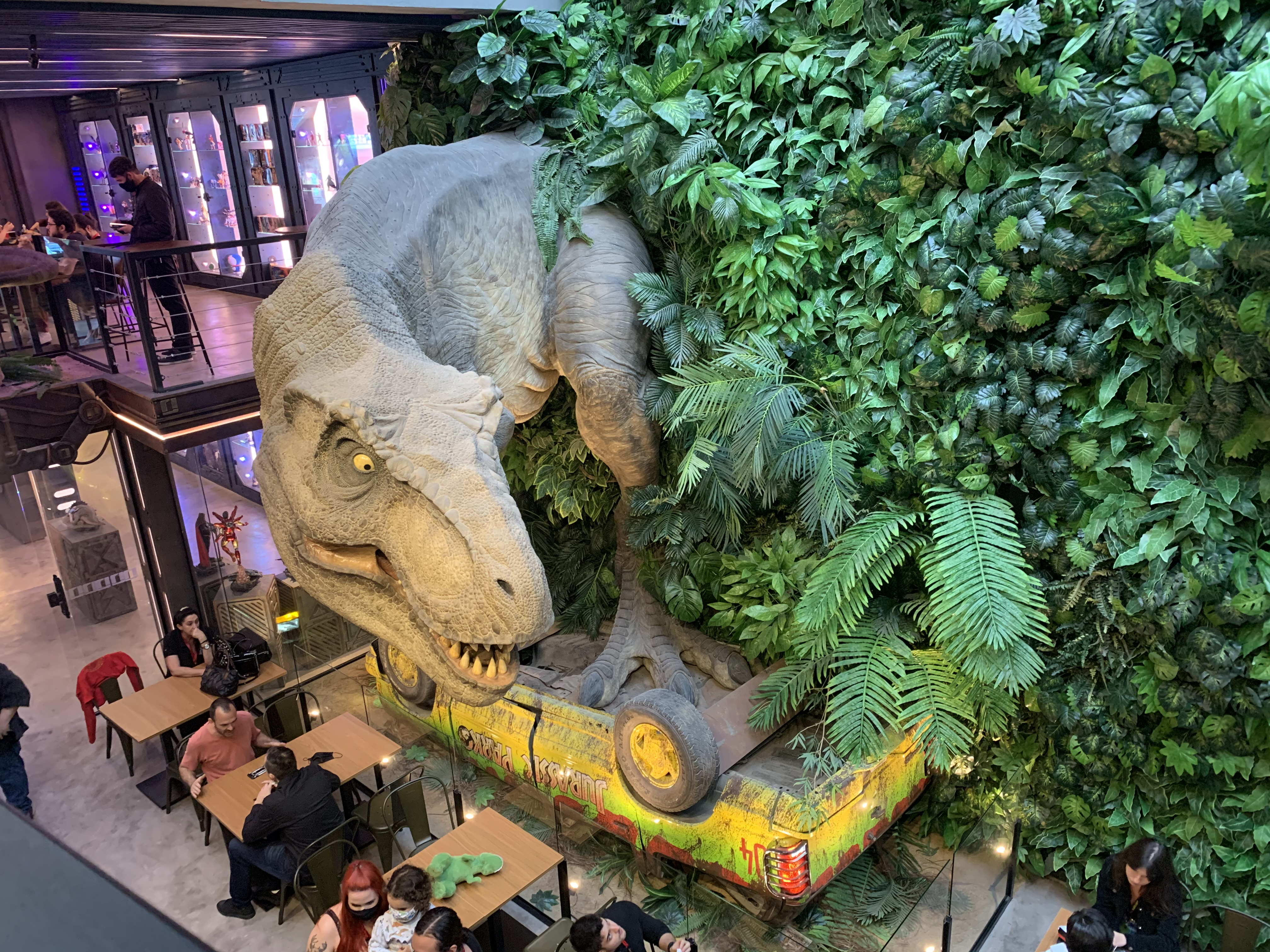 Parede de plantas falsas com uma réplica de um tiranossauro rex sobre um carro virado do Jurassic Park.