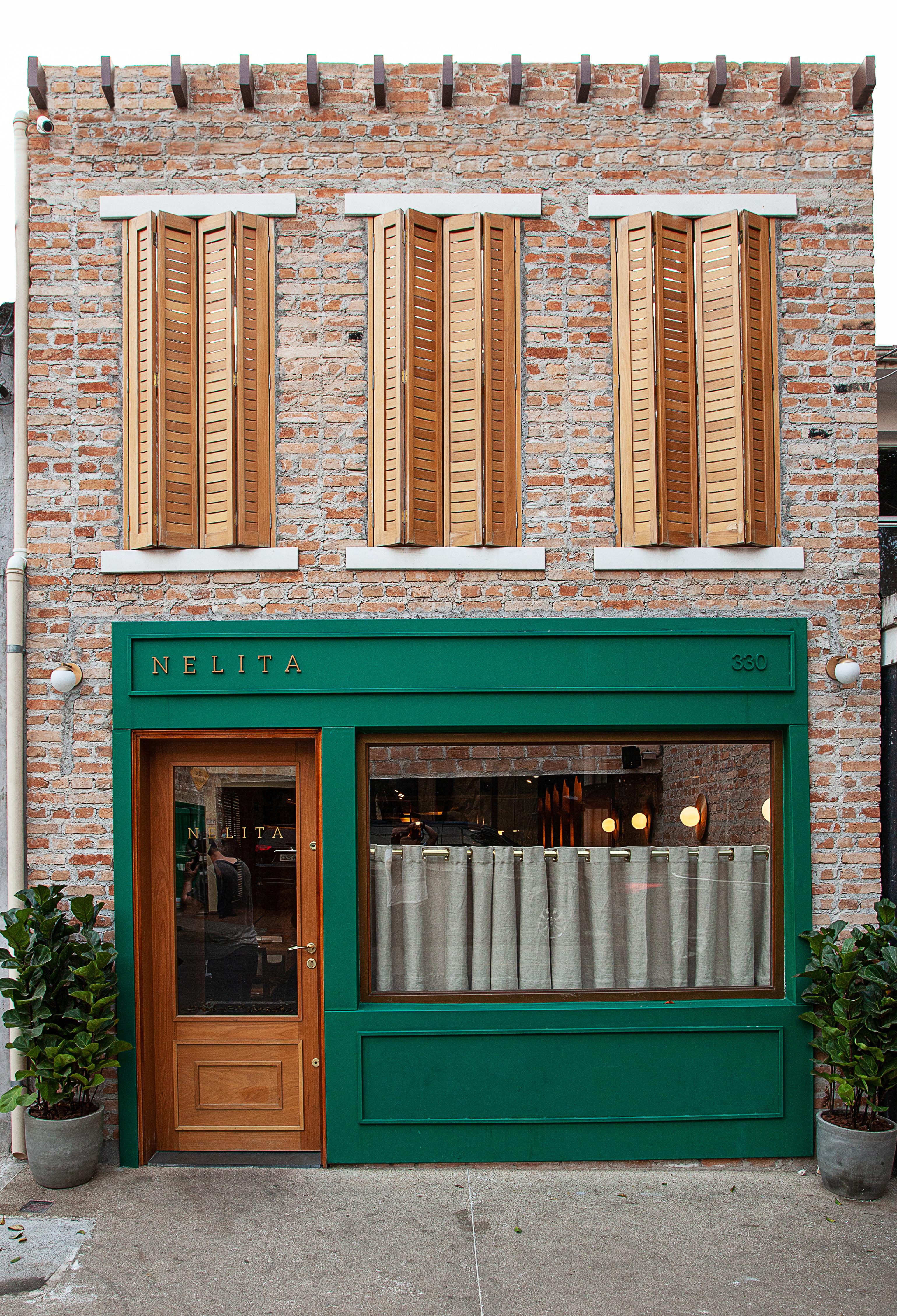 Fachada do restaurante Nelita, com tijolinhos à vista, três janelas de madeira na porção superior e uma janela verde com vidro coberto por cortina embaixo.