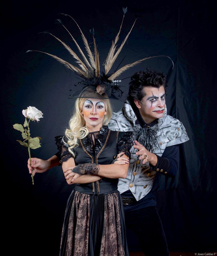 Com roupas de época e maquiagem bem forçada, um casal posa para a câmera. A mulher está de braços cruzados e o homem, por trás dela, segura uma rosa. O fundo da foto é todo preto