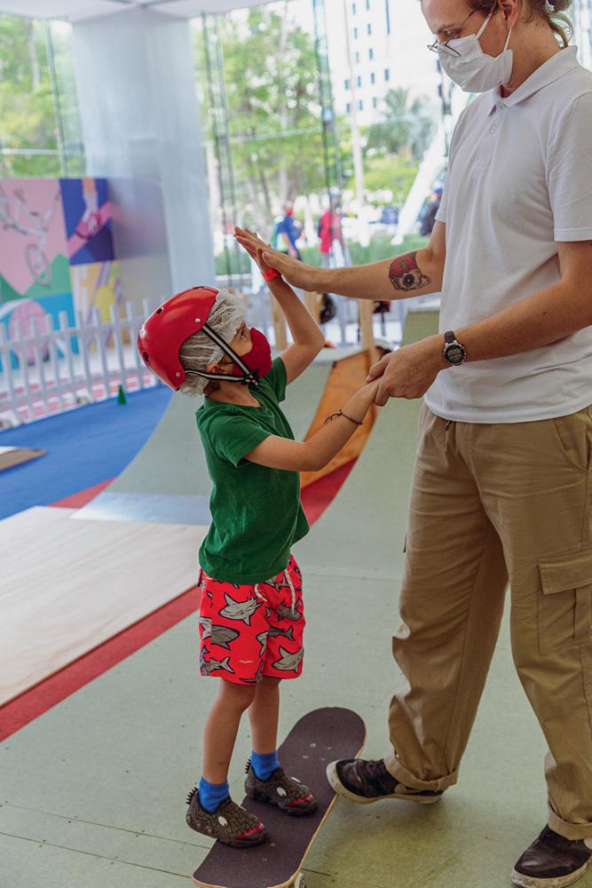 Uma criança, equipada com capacete, está em cima de um skate e bate na mão de um adulto ao lado dele.