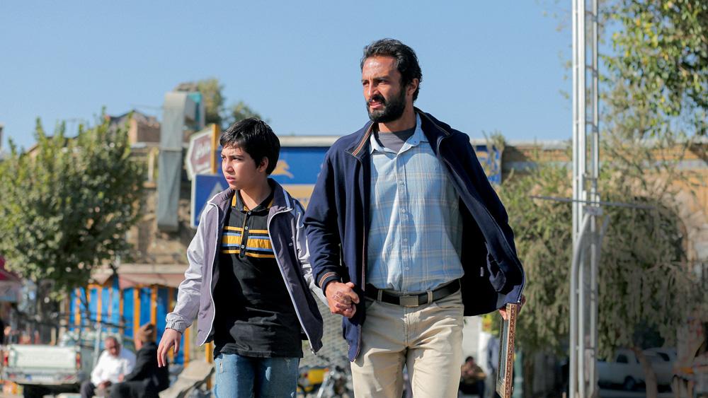 A imagem mostra um adulto e uma criança andando no meio da rua, com o céu azul ao fundo.
