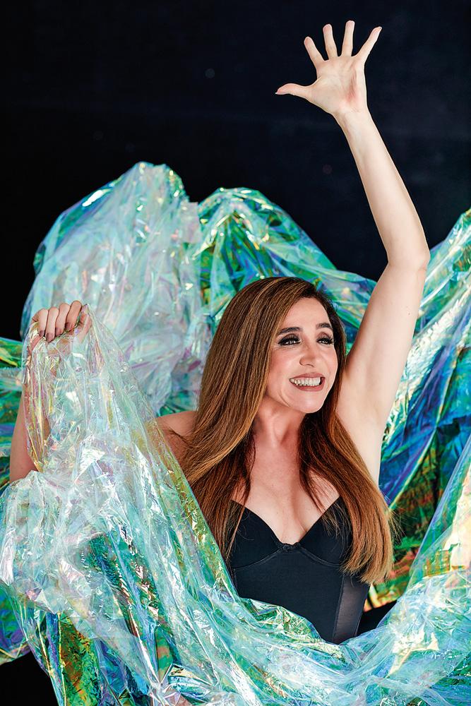 A imagem mostra Marisa Orth no meio de papel celofone azul. Ela está com o braço estendido para cima, a palma aberta enquanto sorri para a frente.