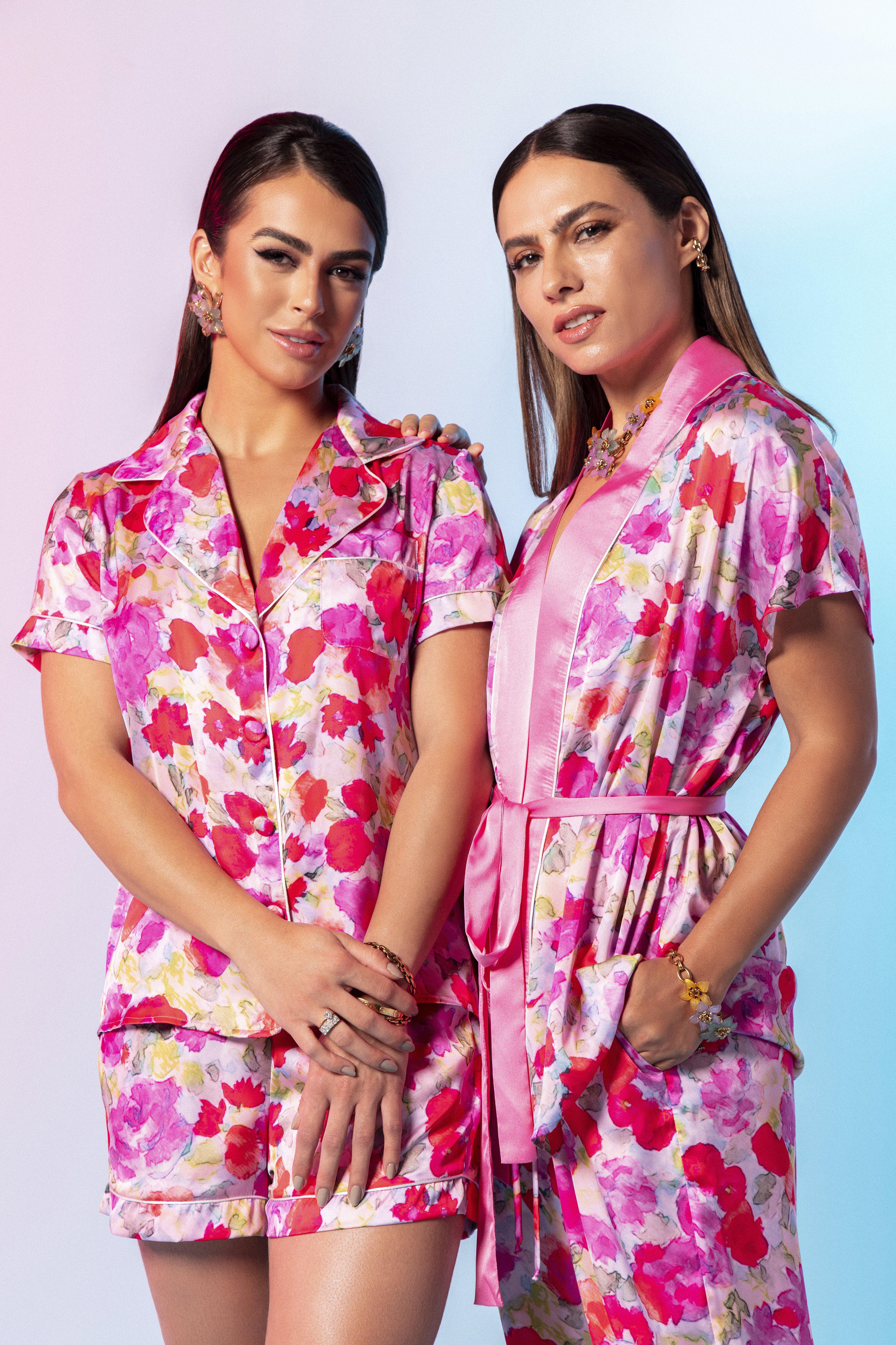 Mari Saad e Patricia Bonaldi posam lado a lado em pijamas rosados com florais.