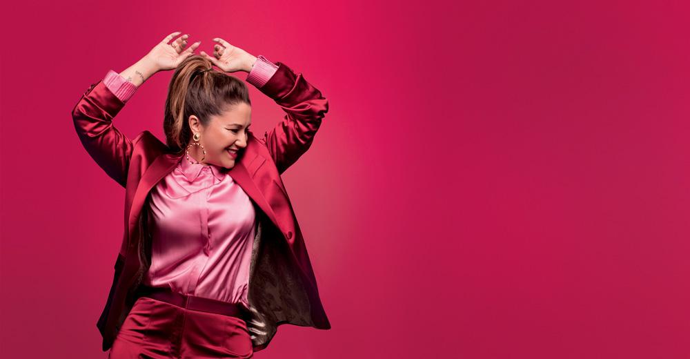 A imagem mostra Paula Toller com os braços para cima como se tivesse dançando, em um fundo rosa.