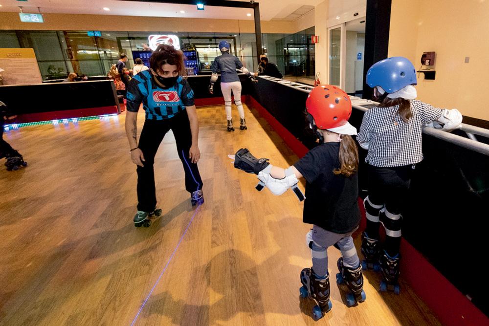 Um monitor auxilia duas crianças a brincarem em uma pista de patinação. Elas estão segurando nas bordas e ele no centro, na frente