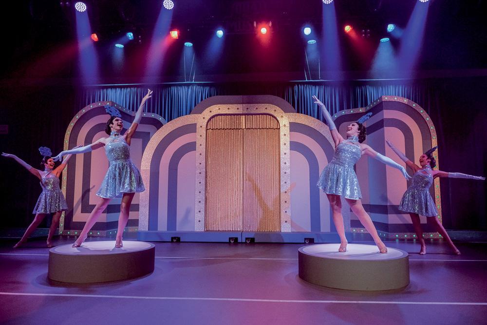 A foto mostra quatro bailarinas em dançando em frente a uma grande porta dourado no espetáculo Silvio Santos Vem Ai.