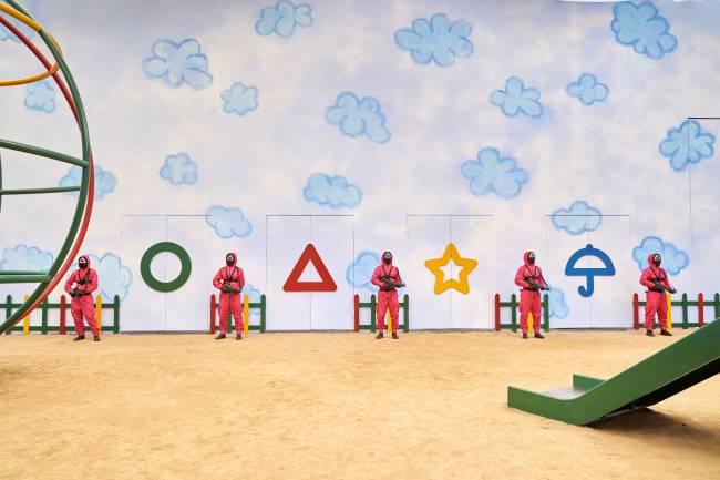 A imagem mostra uma cena da série Round 6, com pessoas mascaradas e com uniformes vermelhos posicionadas lado a lado