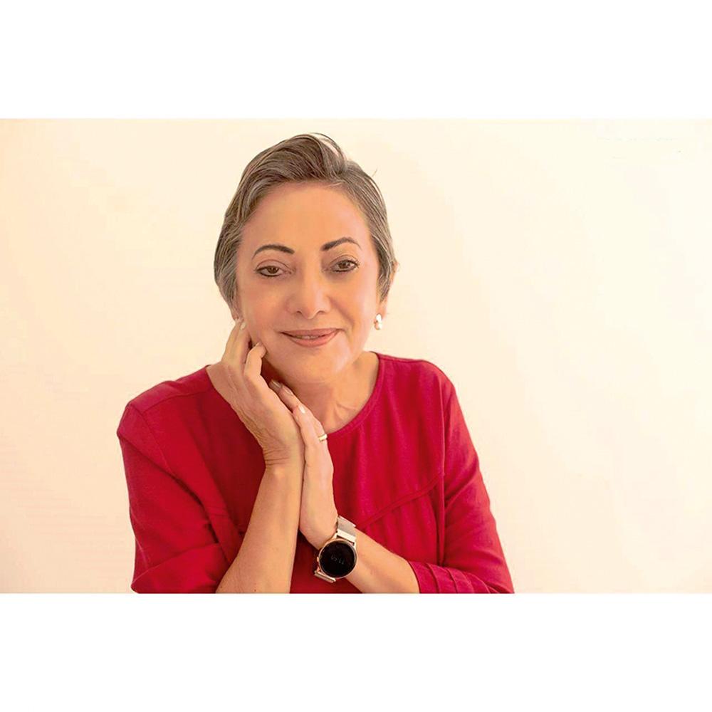Uma mulher posa com uma das mãos perto do queixo e blusa vermelha. Ela olha para a câmera