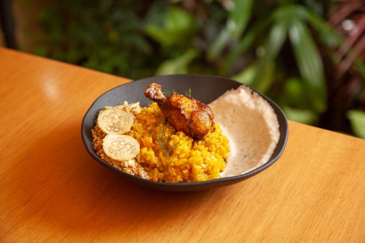 Galinhada servida com farofa, rodelas de pepino e uma coxa de frango