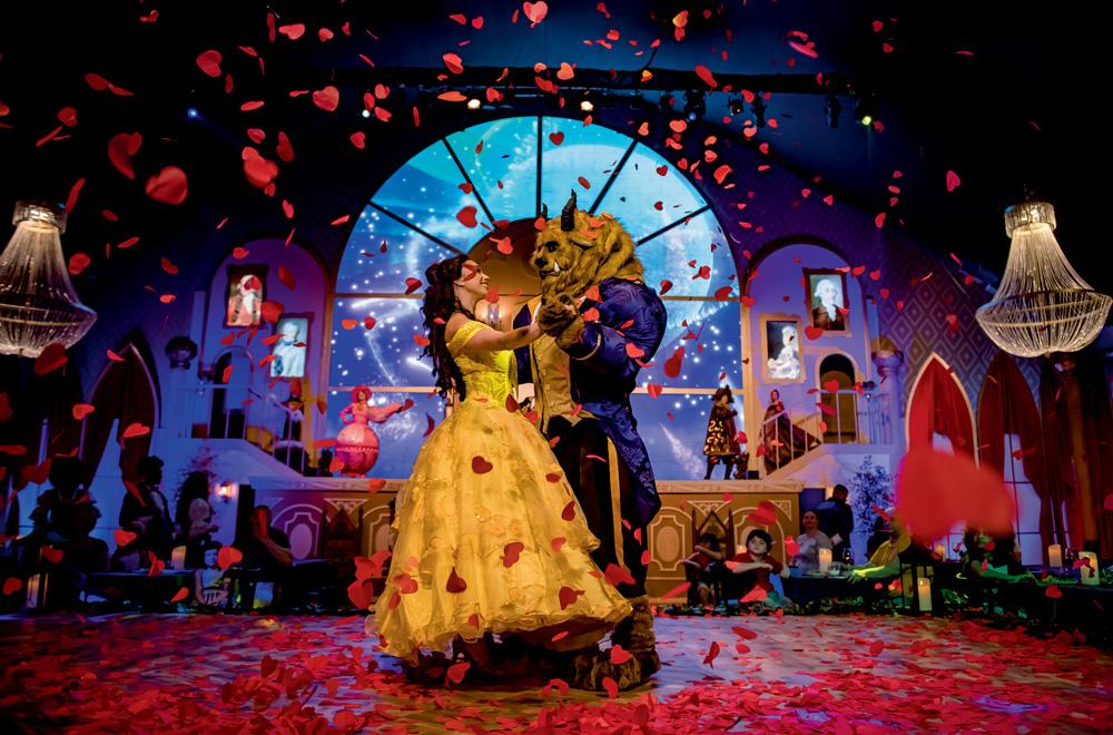 A imagem mostra a atriz da Bela e da Fera dançando no palco em uma chuva de pétalas de rosa.