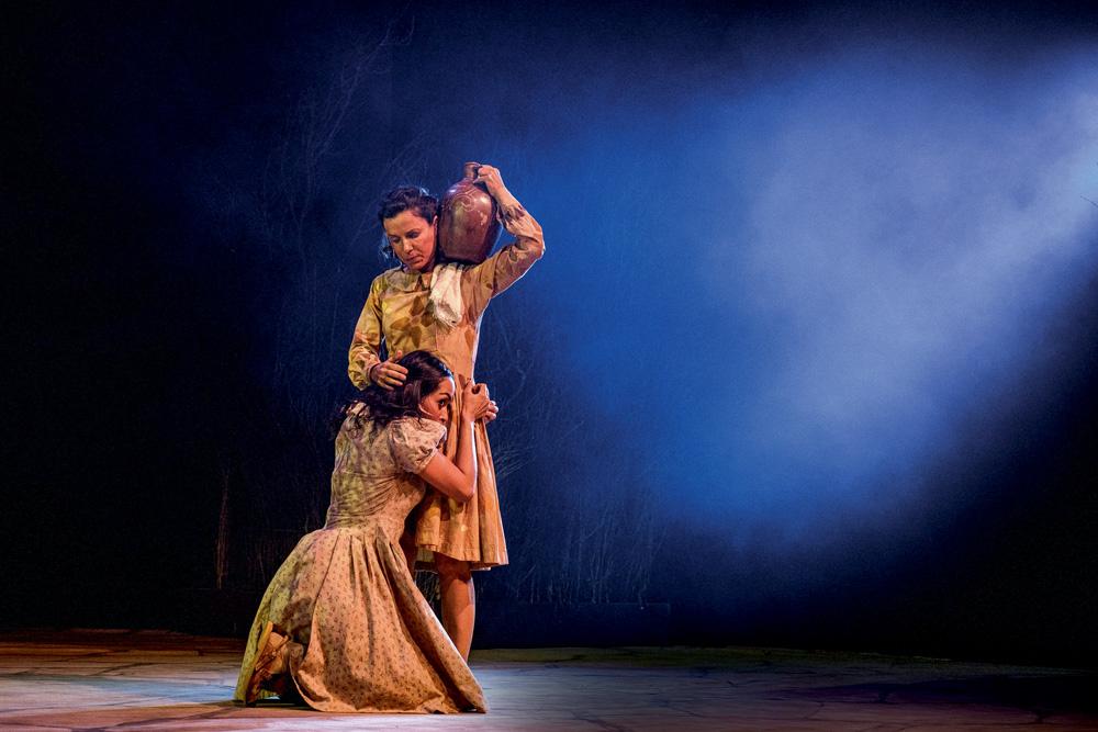 A imagem mostra uma mulheres, com vestes de cangaceiras. Uma carrega um vaso no ombro e outra a abraça na cintura, ajoelhada no chão, enquanto recebe um carinho na cabeça.