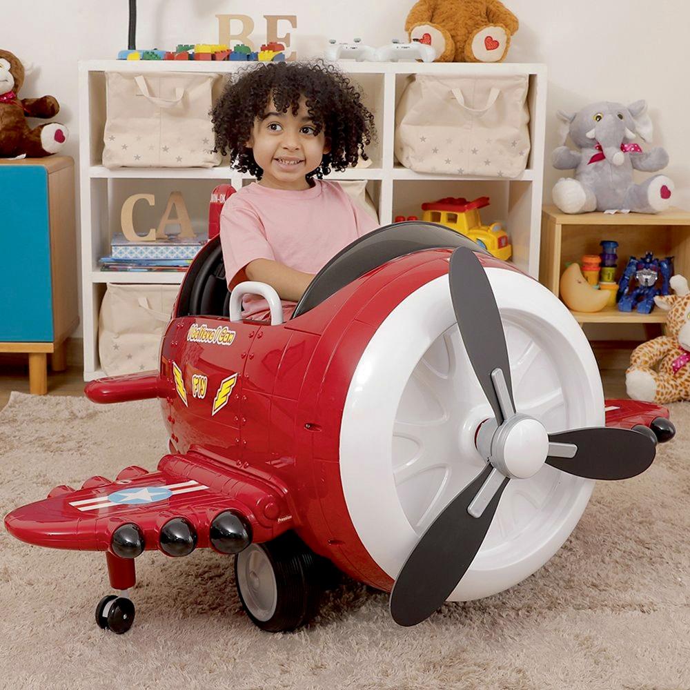 Uma criança sentada em um avião elétrico, como se fosse um carrinho de dirigir