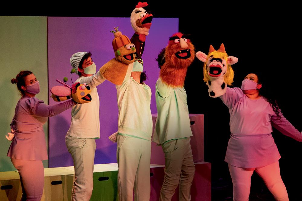 A imagem mostra fantoches conduzidos por atores em cima do palco.