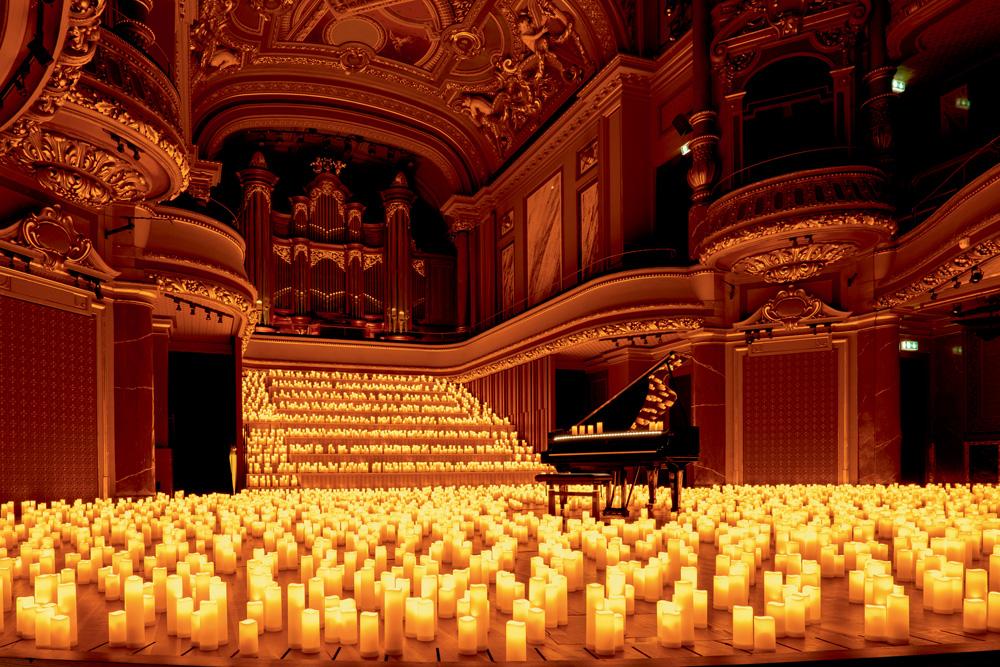 A foto mostra um grande espaço cheio de velas no chão e em uma escadaria larga em frente. Há um piado de calda, com algumas velas em cima no centro do salão.