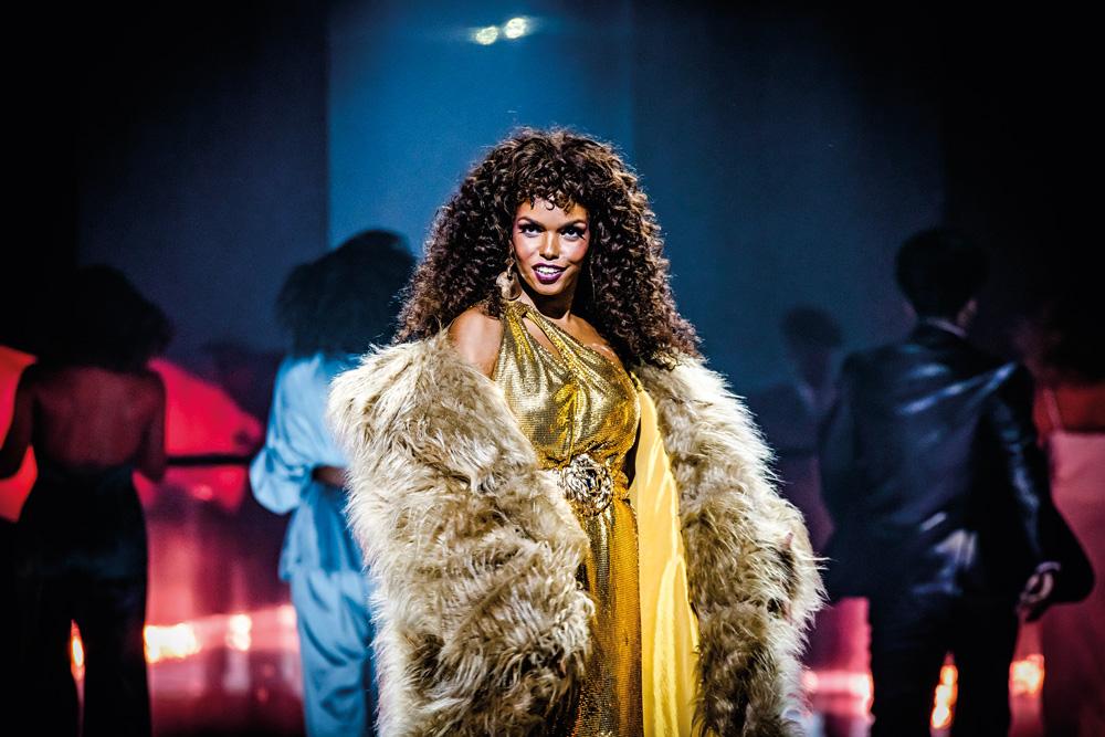 A imagem mostra Jeniffer Nascimento durante a peça Donna Summer. Ela está vestindo um grande casaco com pelos e vestes douradas, enquanto sorri olhando para a plateia.