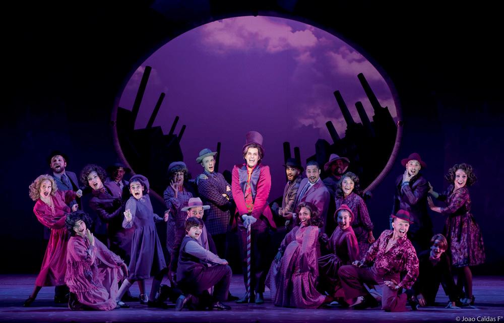 A imagem mostra 19 atores em cima do palco, sorrindo para a plateia com as bocas abertas durante a peça Charlie e a Fantástica Fábrica de Chocolate.