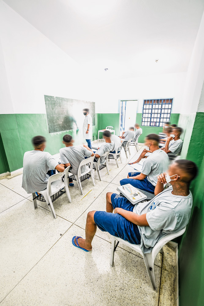 A imagem mostra alunos sentados em cadeiras de plásticos, vendo um professor na frente da sala, escrevendo em uma lousa.