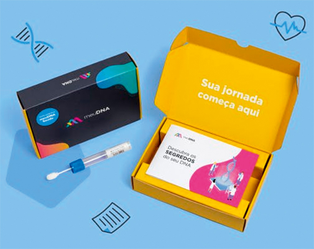 Um teste de coleta da empresa meuDna. Tem uma caixinha amarela com as instruções, uma espécie de cotonete ao lado e uma caixa preta também