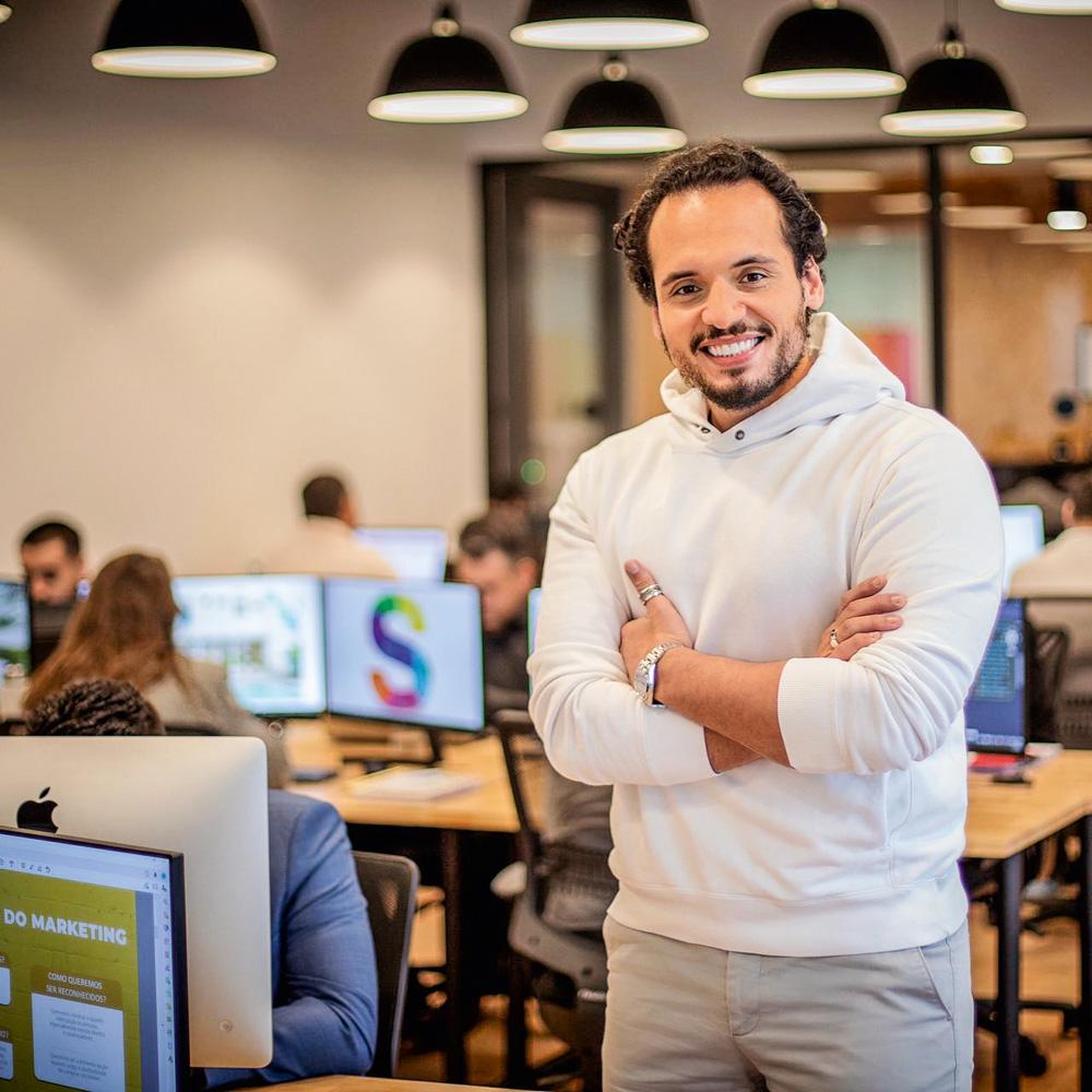 Bruno Sindona sorrindo de braços cruzados com computadores e pessoas trabalhando ao fundo