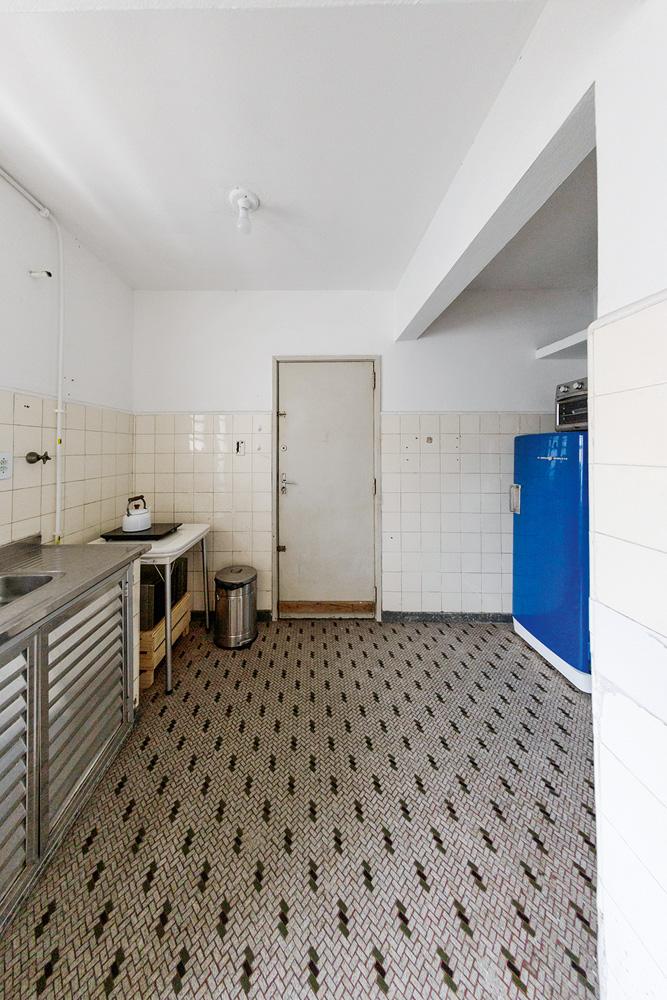 foto da cozinha de matheus ilt antes da reforma, com piso branco com detalhes pretos, parede branca e porta branca ao fundo e pia à esquerda