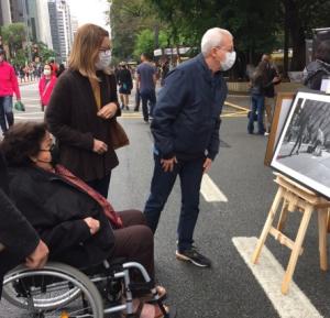Pessoas olhando retratos, que são parte da exposição Arte Na Rua, que acontece na Avenida Paulista