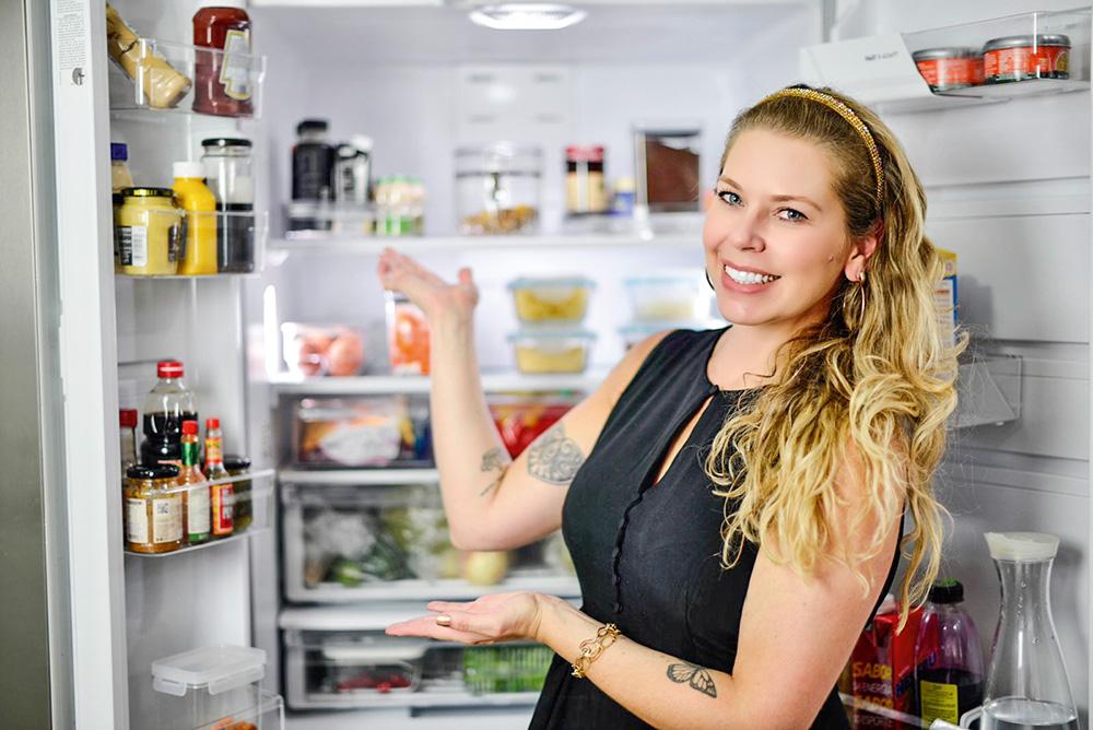 Rafa Oliveira sorrindo apontando, para a foto, para uma geladeira aberta com seus conteúdos organizados
