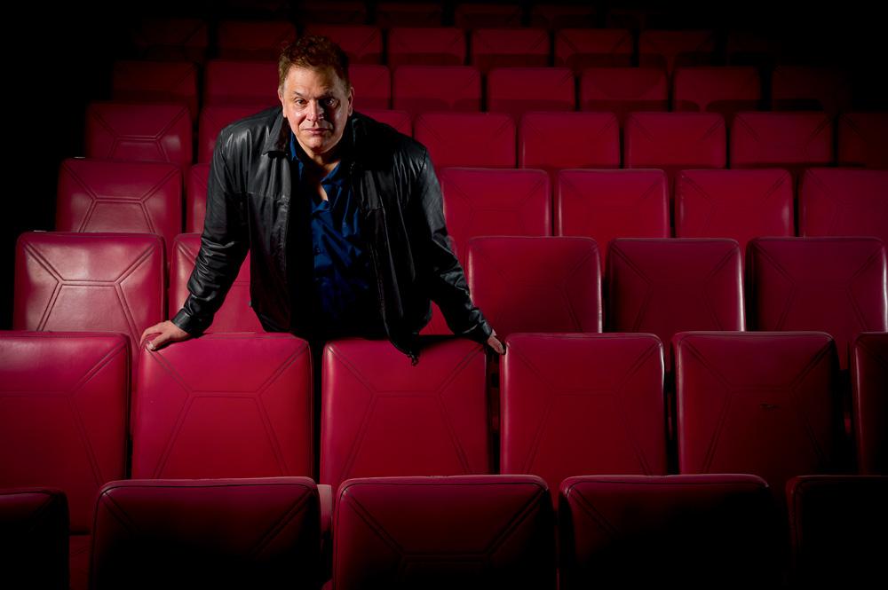 rodolfo posando para a foto com expressão séria em meio a cadeiras da sala do cine bijou, encostado em algumas delas com os braços semiabertos