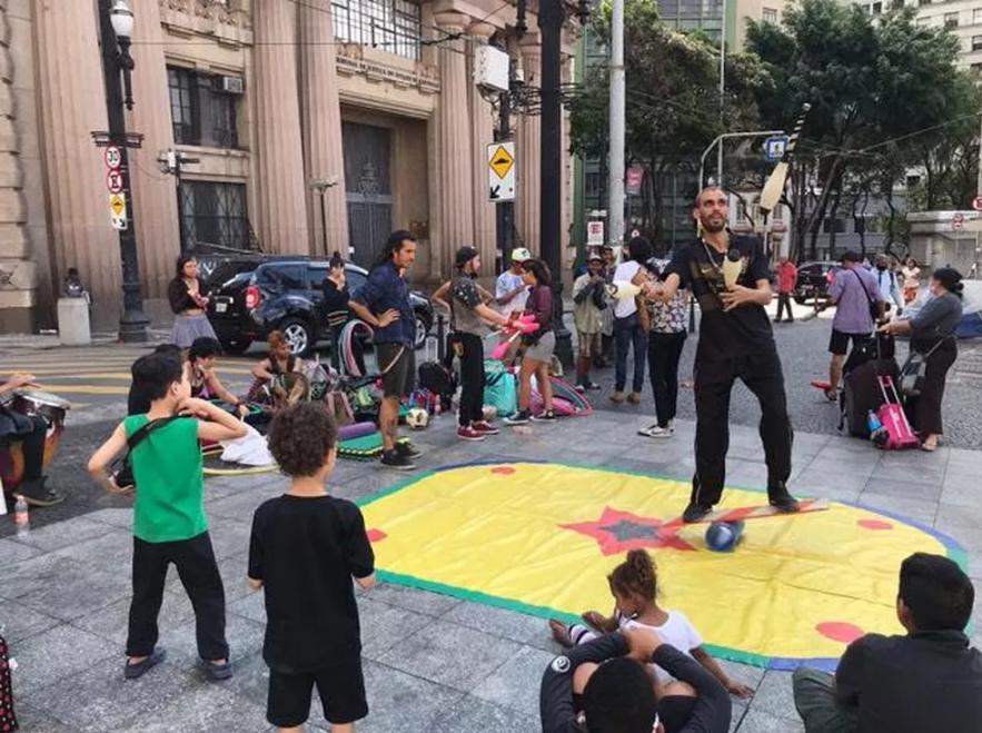 Em uma praça, há crianças em volta de um circulo com um tapete colorido de brincar. Há um homem fazendo malabarismos no centro da roda
