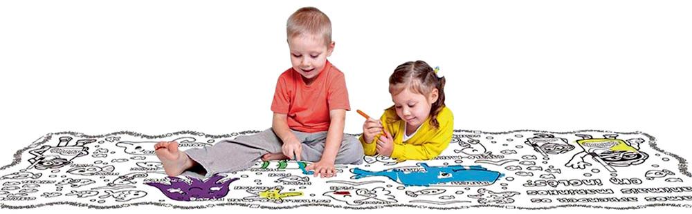 Duas crianças sentam em frente a um tapete de colorir. No tapete, ilustrações diversas de bichos, plantas etc